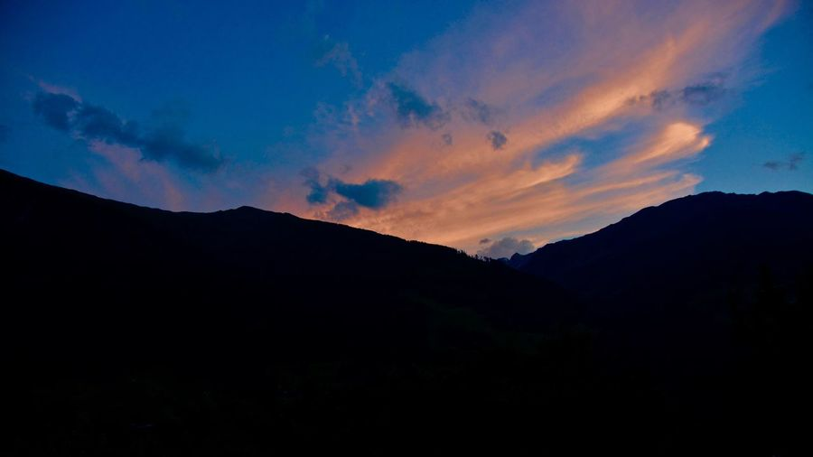 Scenic view of mountains against sky at sunset