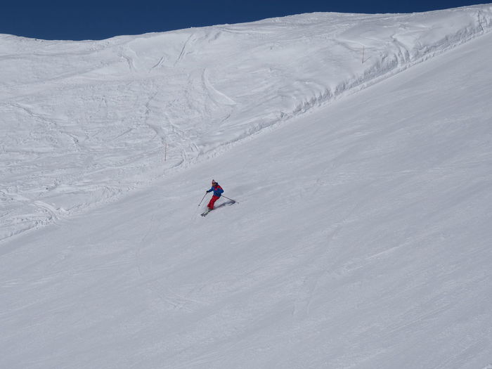 Distant View Of Person Skiing In Snow