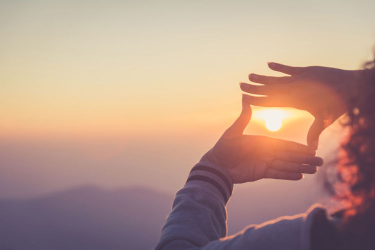 Sunset Sky One Person Hand Human Hand Real People Nature Sun Lifestyles Sunlight Orange Color Leisure Activity Holding Human Body Part Beauty In Nature Copy Space Outdoors Men Tranquility Finger Frame Visual Vision