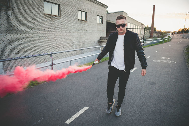 Full length portrait of young man with smoke bomb