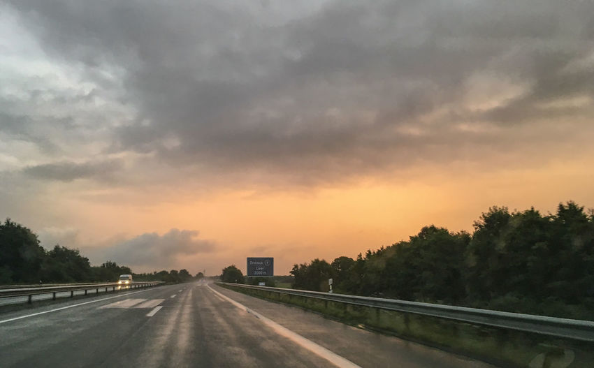 Road against cloudy sky at sunset