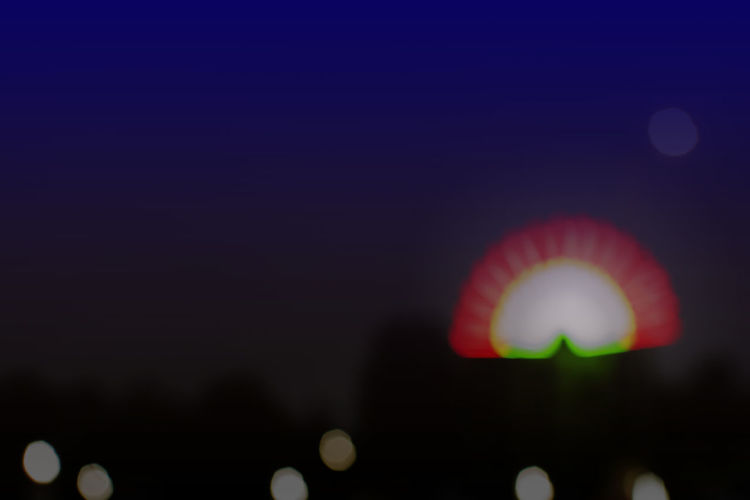 Defocused image of illuminated ferris wheel against sky at night