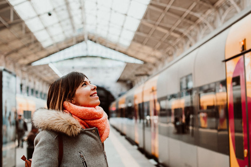 Woman standing by train at railroad station