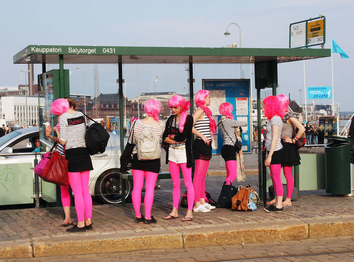 Colors Pink Waiting Architecture Building Exterior Built Structure Busstop Casual Clothing City Day Fashion Full Length Lifestyles Medium Group Of People Musician Neon Color Neon Life Neon Pink Outdoors Pink Color Real People Standing Street Women Mix Yourself A Good Time