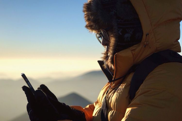 Close-up of hiker using phone on mountain against sky