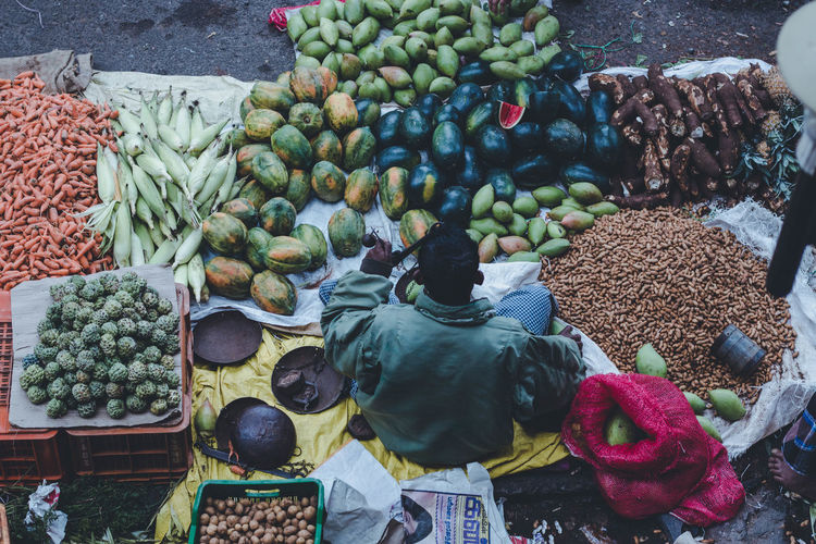 Rear view of man selling fruits and vegetables at market