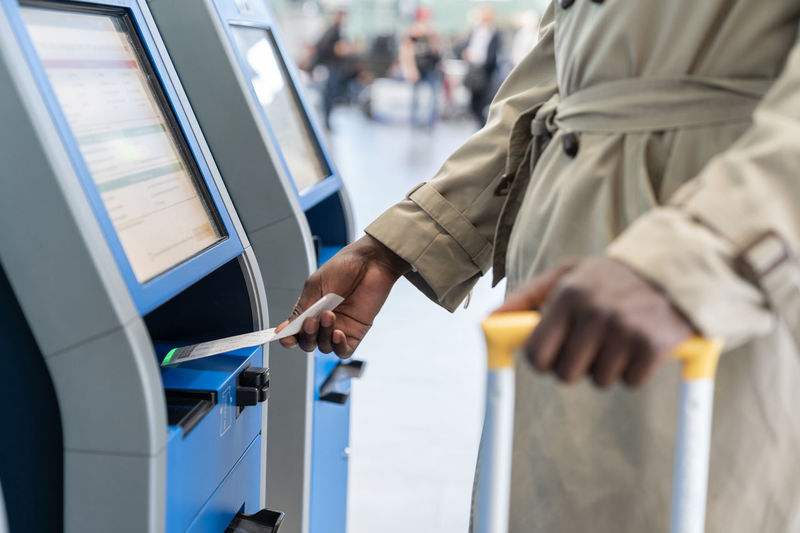 Midsection of woman using self check in kiosk at airport