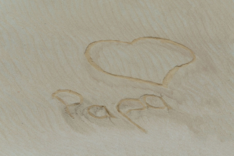 Golden sand with a subscribed in the sand heart and the word Dad. Beach Trourism Close-up Dad Day Heart Shape Holiday Love No People S Script Tranquility Working