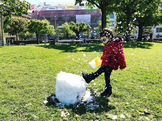 Kick Grass Real People Full Length Park - Man Made Space Outdoors One Person Day Tree Lifestyles Sunlight Walking Green Color Girls Leisure Activity Motion Architecture Childhood Nature Growth Playing Kick Boy Snow Sport