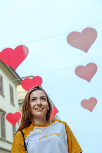 Smiling woman against heart shape decoration in city