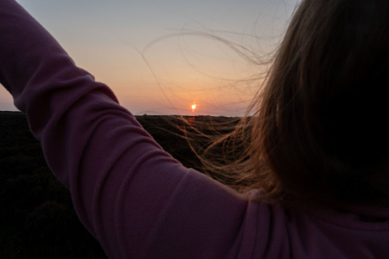 Close-up portrait of woman hand against sky during sunset