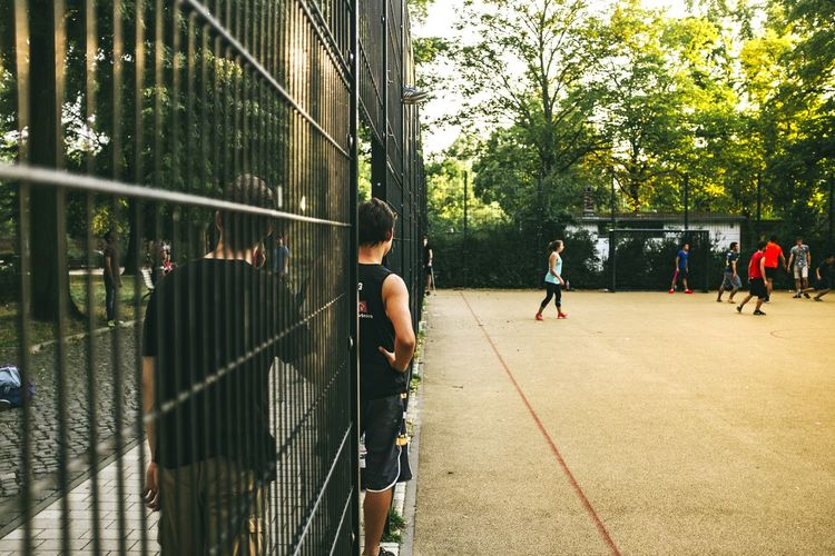 Man amidst metallic wall looking at people playing soccer on field