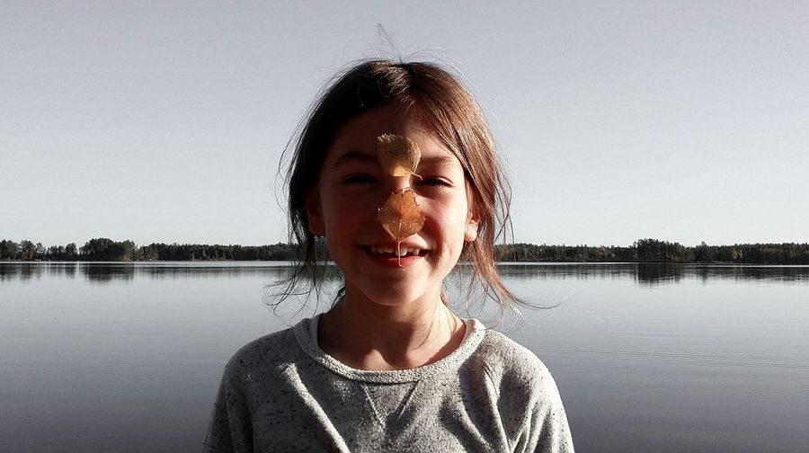 Portrait of girl with leaves on nose against lake and clear sky