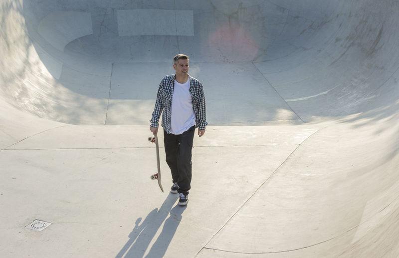 Man with skateboard walking on ramp in park