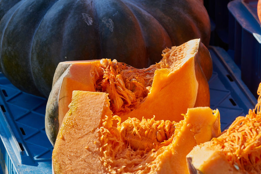Sliced pumpkin with colorful orange fruit pulp inviting for taste on a local market - green pumpkin in the background Colorful Eatng First Eyeem Photo Freshness Green Color Healthy Local Landmark Low Carb Nature Nature_collection Orange Color Pumpkin RGanimals Vegetable