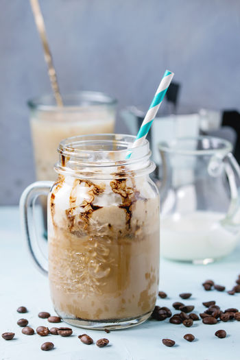 Glass mason jar with ice coffee with whipped cream, ice cream and chocolate sauce, served with coffee beans, coffe pot and jug of milk over light blue textured background. Food And Drink Drink Refreshment Glass Food Freshness Coffee Coffee - Drink Iced Coffee Frappe Cold Drink Glass - Material Coffee Beans Cocktail Table Jar Straw Drinking Straw Drinking Glass White Whipped Cream Milk