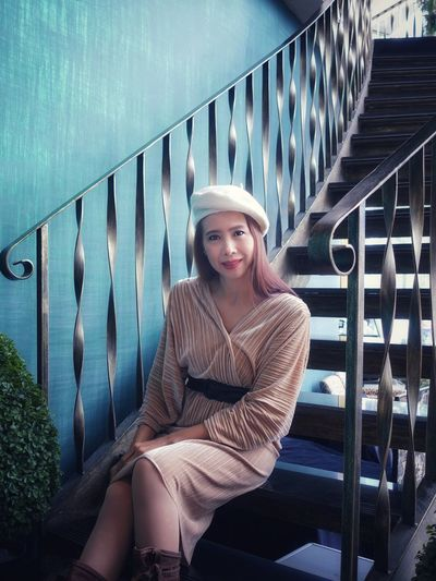 Portrait of smiling young woman sitting staircase against railing