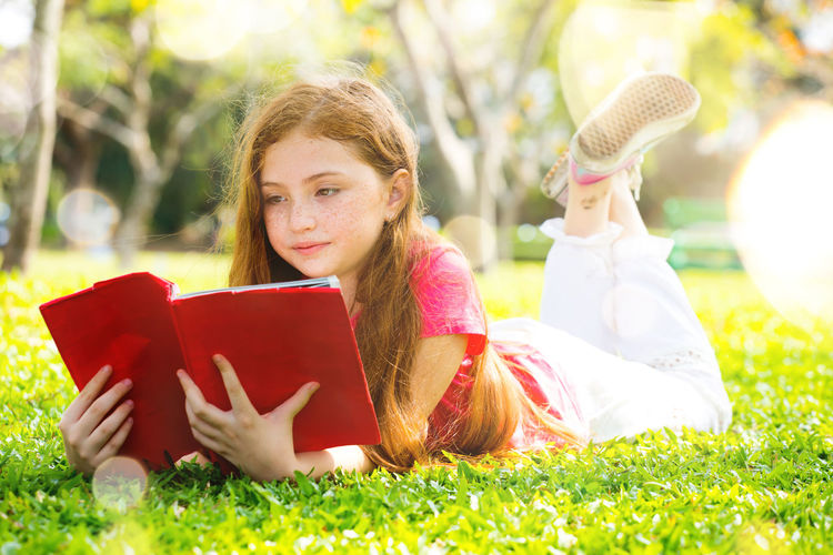 Girl reading book while lying on lawn