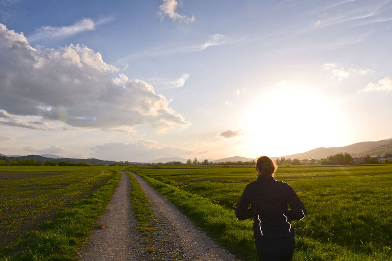 Mid adult woman jogging on land against sky during sunset