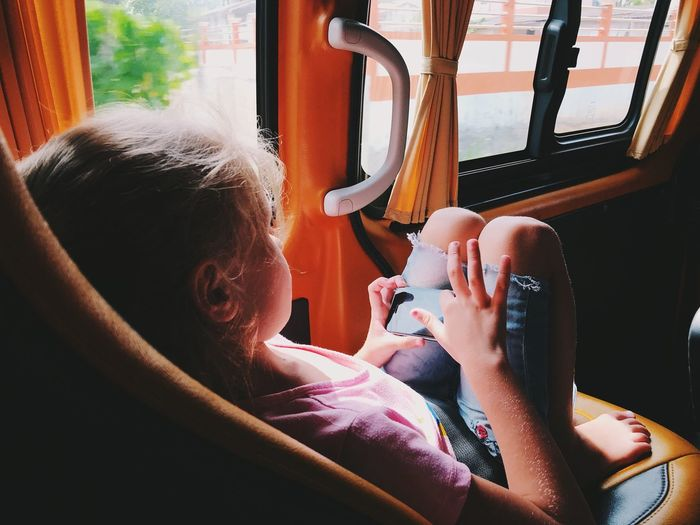 Girl using smart phone while sitting in bus