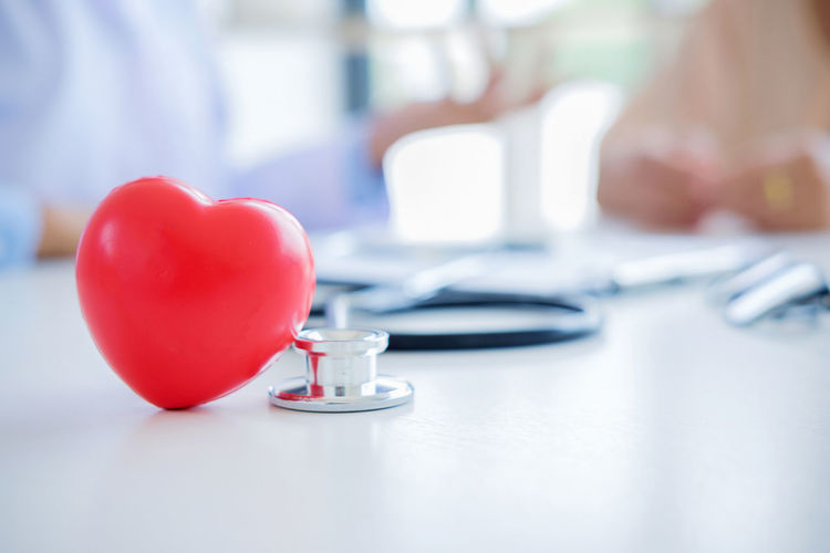Close-Up Of Red Heart Shape With Female Doctor And Patient At Desk In Hospital