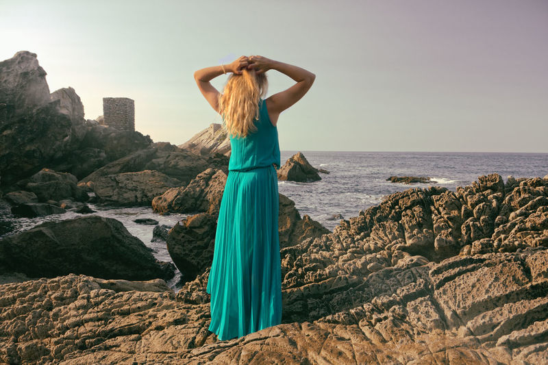 Rear view of mid adult woman with hands behind head standing on rock by sea against sky