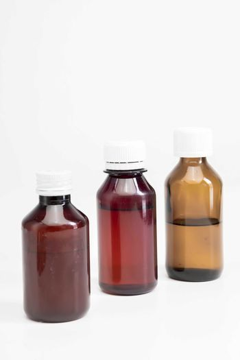 Bottle of medicine White Background Studio Shot Healthcare And Medicine Bottle Container Medicine Indoors  Cut Out Glass - Material No People Close-up Copy Space Pill Still Life Group Of Objects Science Lid Transparent Three Objects Choice