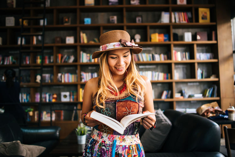 Portrait of smiling young woman reading book