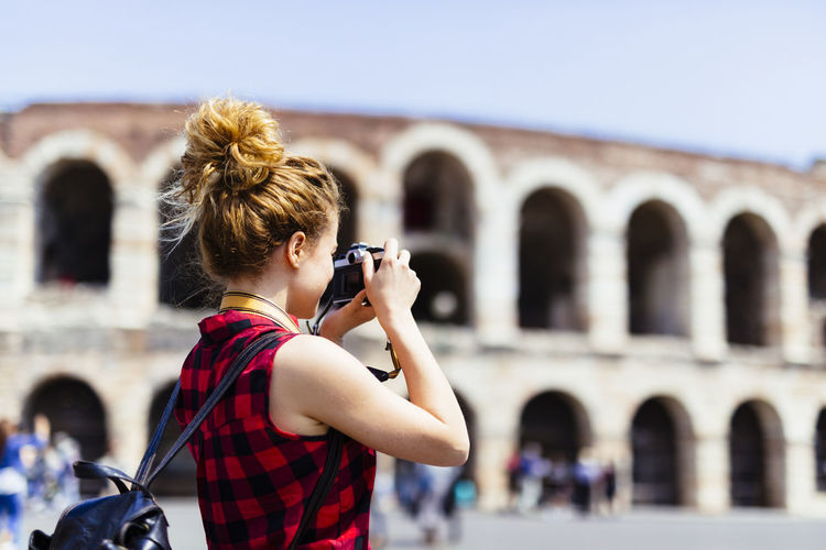 Woman photographing against built structure