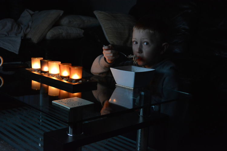 Young boy eating in living room at night