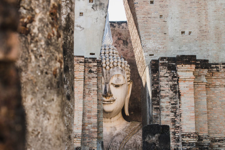 Statue of buddha against wall of building