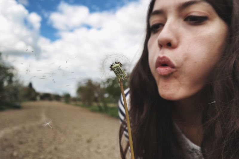Close-Up Of Young Woman Blowing Dandelion Seeds Against Sky