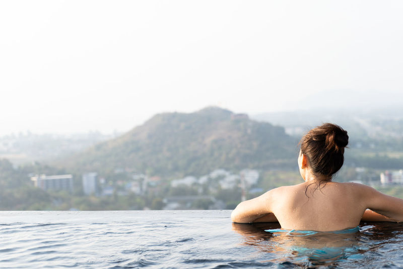 Rear view of woman in infinity pool against clear sky