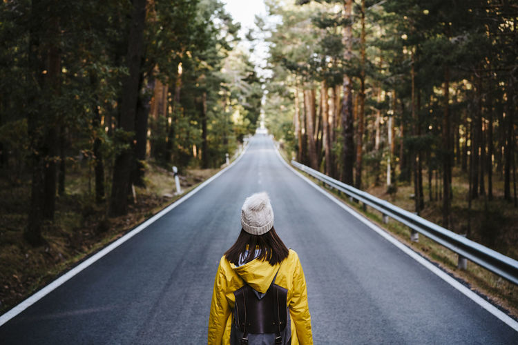 Rear view of person on road amidst trees in forest