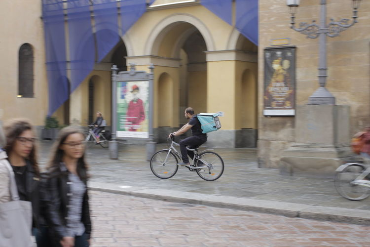 People riding bicycle on street against building
