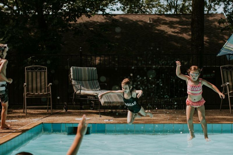 Swimming Pool Water Fun Enjoyment Leisure Activity Candid Motion Outdoors Day People Friendship Real People Happiness Full Length Boys Cheerful Tree