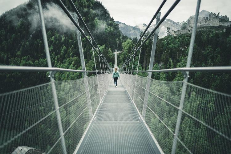 Rear view of person walking on footbridge