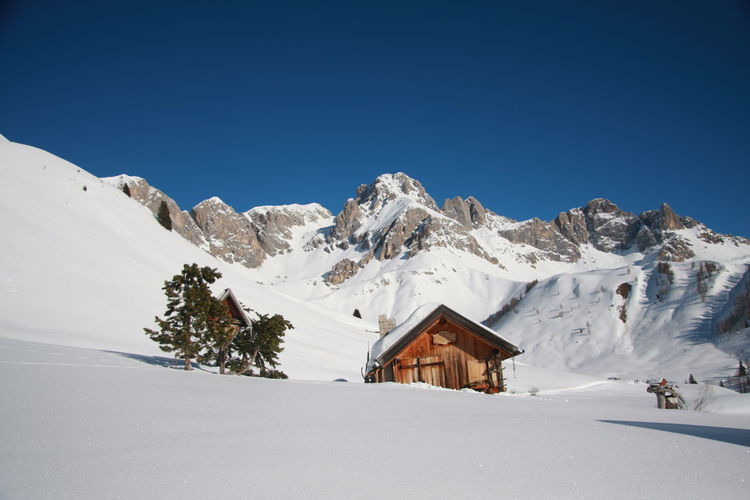 House and snowcapped mountains against clear blue sky