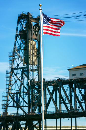 American flag waving in front of the Steel Bridge in Portland, Oregon American Flag Architecture Blue Bridge Built Structure City Day Downtown Flag No People Northwest Oregon Outdoors Pacific Northwest  Patriotism Portland River Sky Steel Bridge Tourism Travel Travel Destinations Urban USA Willamette River