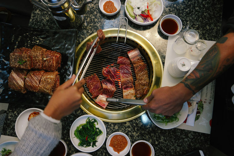 Traditional Korean grill beef. Adult Adults Only Barbecue Celebration Chef Day Dining Table Dinner Party Domestic Life Food And Drink Human Body Part Human Hand Indoors  Korean Food Korean Grilled Beef One Person Only Women People