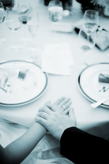 High angle view of hands on table at restaurant