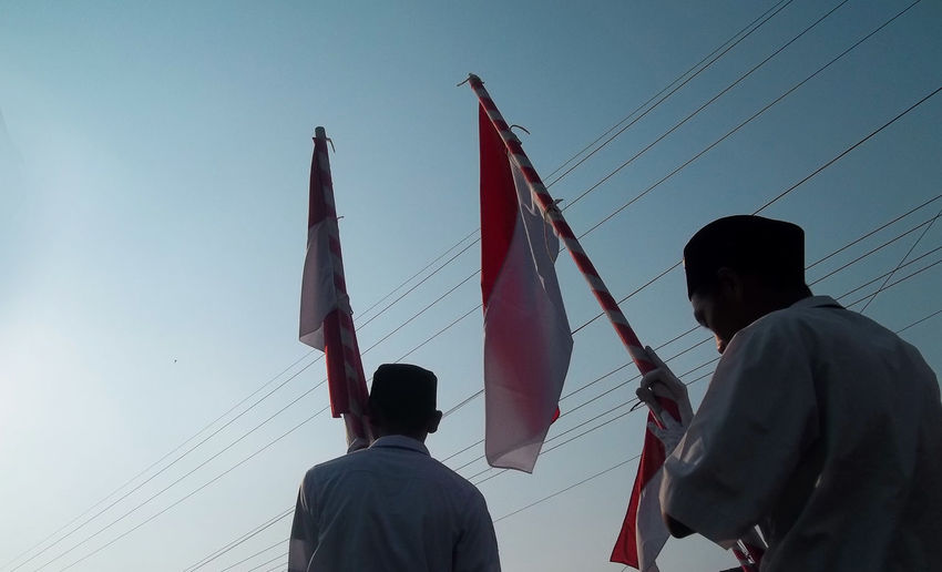 Low Angle View Of People Holding Flags While Standing Against Clear Sky