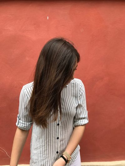 Teenage girl with long hair standing against red wall