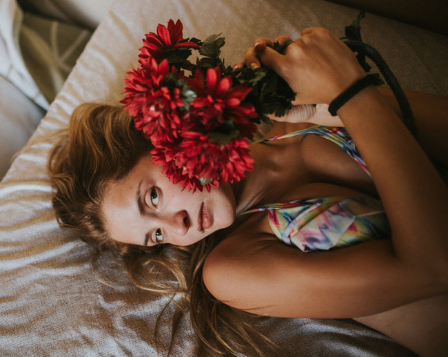 High Angle Portrait Of Beautiful Woman Lying With Flowers On Bed At Home