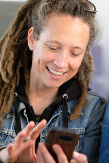 Close-up portrait of a smiling young woman using mobile phone