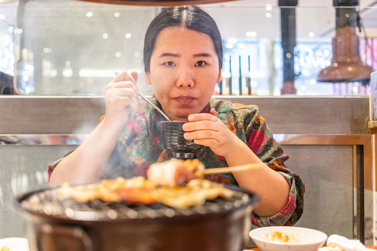 Portrait of woman eating food by barbecue grill in restaurant