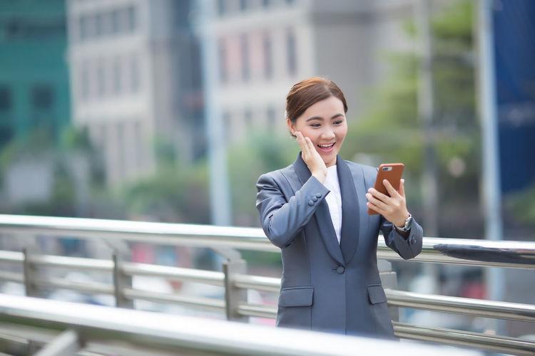 Smiling businesswoman using mobile phone on bridge in city