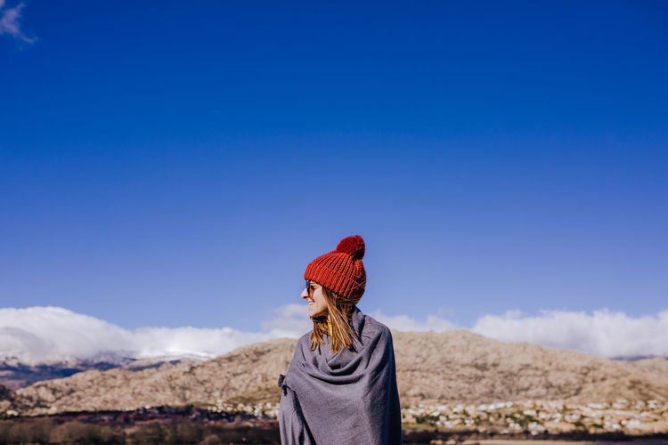 Rear view of person standing against blue sky