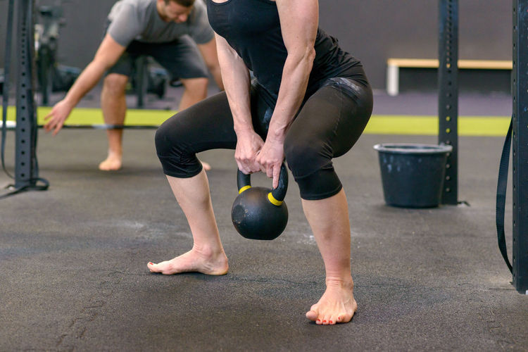 Low Section Of Female Athlete Exercising With Kettlebell In Gym
