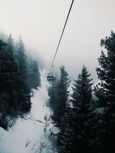 Ski Lifts Over Snow Covered Landscape During Foggy Weather